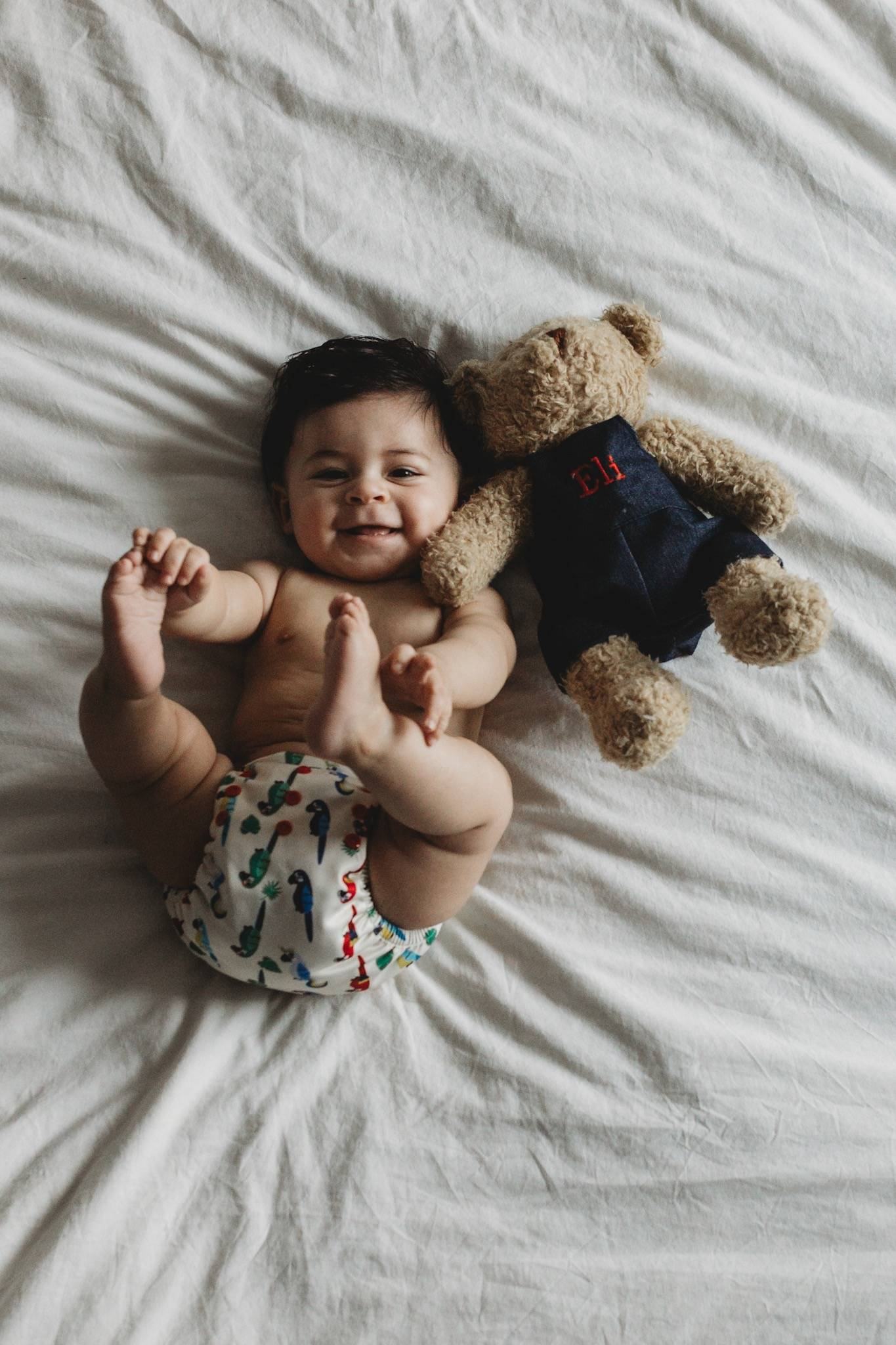 A photo of a baby with a stuffed bear next to him.